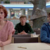 Three students sit in a library with expressions of shock.