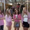 A group of teenage girls all dressed in pink stand in a shopping mall with looks of shock and amusement as one of them speaks on the phone.