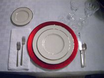 Place setting with red charger.