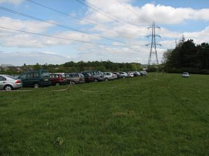Temporary car park. Cars park in a field by th...