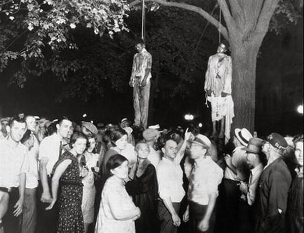 Taken by Lawrence Beitler during 1930. This hanging of two black men was due to a lie that they raped a white girl. This Photograph was used to show the Diplomacy of Whites during that age.