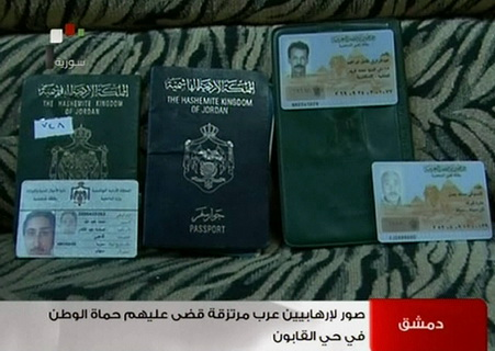 An image grab taken from footage broadcast by Syrian state TV on 22 July shows Jordanian and Egyptian passports and ID cards which were allegedly found on the bodies of gunmen killed during clashes with Syrian security forces in the Qabun district of the capital Damascus