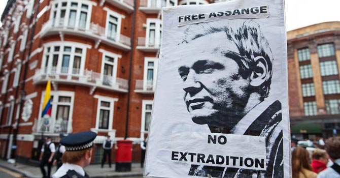 A sign showing a portrait of WikiLeaks founder Julian Assange is held by a supporter outside the Ecuadorian Embassy in London on 16 August 
