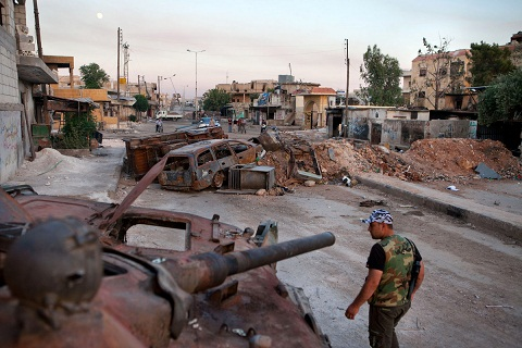 A member of the Free Syria Army walks past a destroyed Syrian forces tank in the town Atareb in northern Aleppo province. (AFP/ File Photo)