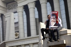 Two men hold a portrait of President Morsy as hundreds of his supporters protest outside a top Egyptian court, forcing judges to postpone a hearing on a constitutional panel at the heart of a deepening political crisis AFP Photo / Mahmoud Khaled