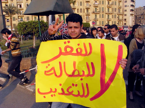 An Egyptian protester carrying a banner saying: No to poverty, No to Unemployment, No to Torture (AFP Photo)