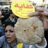 An Egyptian supporter of the Kefaya movement holds up a loaf of bread and an onion during a protest in front of the Sayyeda Zeinab Mosque in Cairo, 18 January 2007. (AFP File Photo)