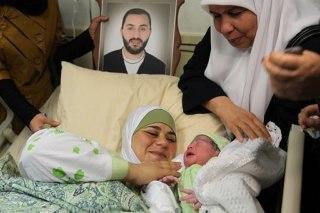 Dallal melihat bayinya yang baru lahir dengan foto suaminya yang sedang dipenjara Israel, Amer al-Zein, 13 Agustus 2013. (AFP, Jaafar Ashtiyeh)
