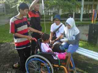 Relawan menyuapi anak gizi buruk (tasya) sambil ngajak jalan2 pagi