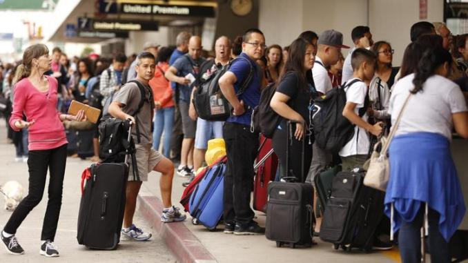 Passengers wait in long lines at LAX due to a recent data center outage.