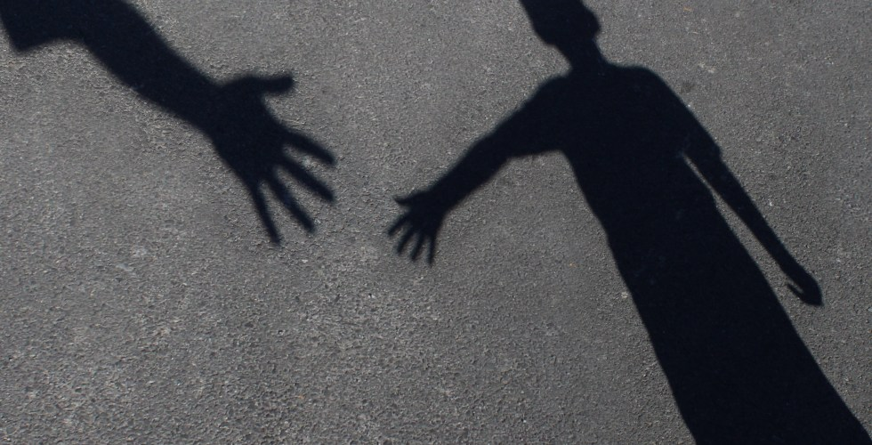 Helping Hand with a shadow on pavement of an adult hand offering help or therapy to a child in need as an education concept of charity towards needy kids and teacher guidance to students who need tutoring.