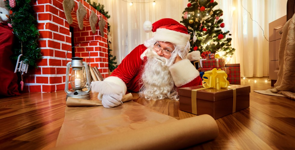 Santa Claus at Christmas, New Year's Eve wrote a list of gifts to children on paper in the room with the Christmas tree and fireplace.