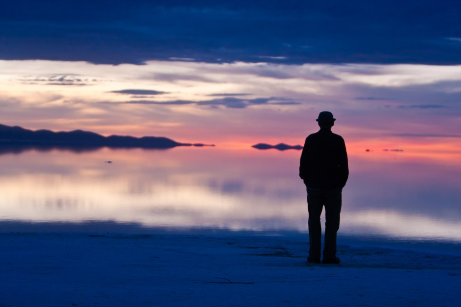 A fellow traveler stands on the edge of the Salar de Uyuni at sunrise. The water, so thickly saline, held reflections unlike anything I'd ever seen. Despite a light breeze blowing, the water barely seemed to ripple.