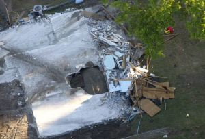 First look inside: An aerial view shows the sinkhole in Seffner, Florida which opened up last Thursday and swallowed Jeff Bush from his bedroom