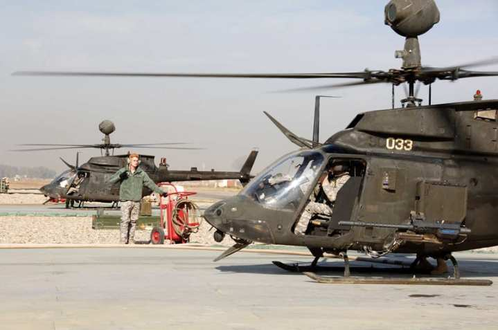 U.S. Army Spc. Deren Stocks, assigned to 1st Aviation Cavalry Squadron, 230th Sustainment Brigade, Tennessee Army National Guard, stands by as his partner fuels a OH-58 Kiowa Warrior helicopter at Forward Arming and Refueling Point, on Forward Operating Base Diamondback, near Mosul, Iraq, Dec. 4, 2009. U.S. Army photo by Pvt. 1st Class Ali Hargis