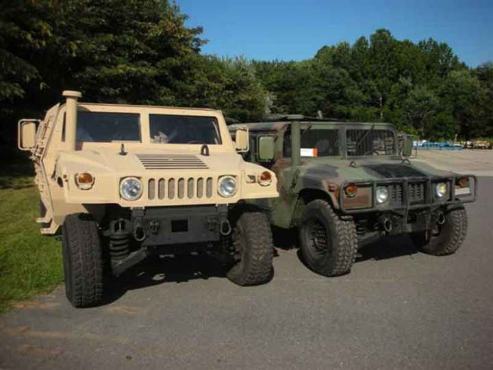 A HMMWV modified with a Small Combat Tactical Vehicle Capsule (left) next to a standard HMMWV. Photo by Scott R. Gourley