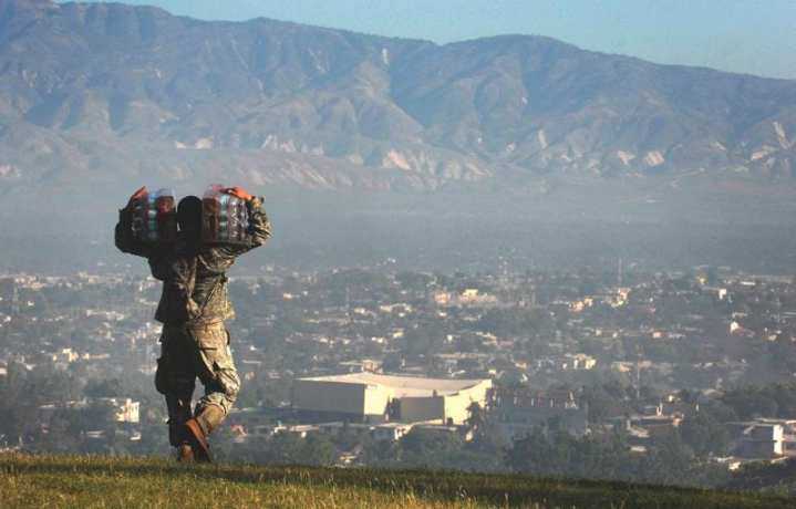 A soldier carries cases of water toward the distribution point at the forward operating base set up by the 82nd Airborne Division's 1st Squadron, 73rd Cavalry Regiment, in Port-au-Prince, Haiti, Jan. 18, 2010. That day the squadron passed out more than 15,000 bottles of water and 4,000 meals. U.S. Army photo by Fred W. Baker III, American Forces Press Service.