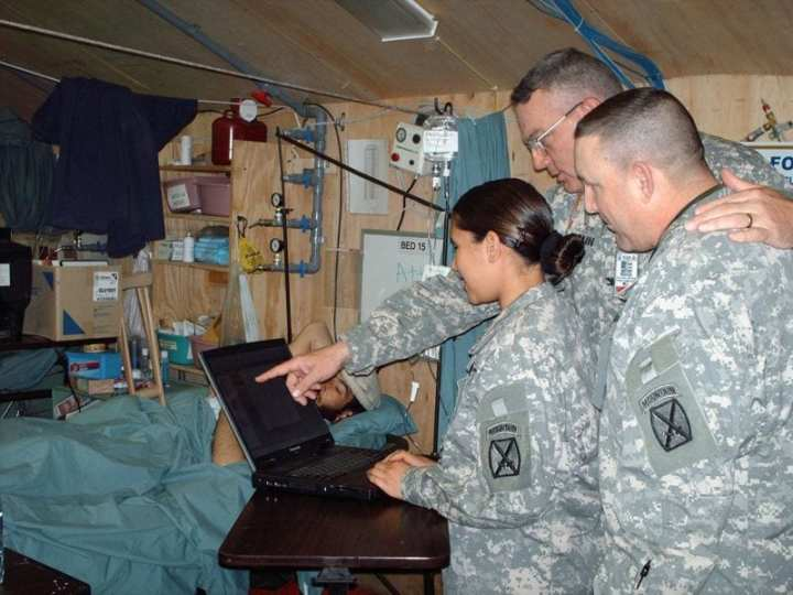 Col. Jeffery Haun, commander of the 14th Combat Support Hospital, Bagram Air Field, Afghanistan (center) reviews medical data on the MC4 system with providers. Photo courtesy of MC4 PAO.