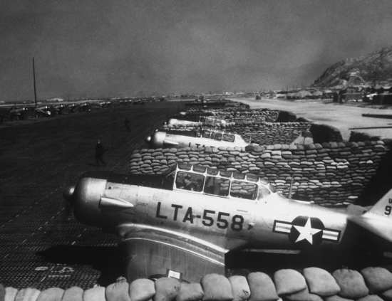 "North American T-6s are shown parked in a revetment area at an advanced airstrip somewhere in Korea.  These T-6 ""Texans"" have proved invaluable in spotting targets and directing the heavily gunned fighters to their objectives by radio.  AIR AND SPACE MUSEUM photo"