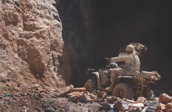 A soldier from the 1st Battalion, 3rd Special Forces Group, rides an all-terrain Vehicle (ATV), into a cave to check for munitions, on the outskirts of Kabul, Afghanistan, July 19, 2002. U.S. Air Force photo by Senior Airman Bethann Hunt