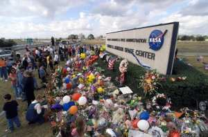 In memory of the Space Shuttle Columbia crewmembers who lost their lives on February 1, 2003, a massive collection of flowers, balloons, flags, signs, and other arrangements were placed at the Johnson Space Center sign at the Center's main entrance. NASA photo