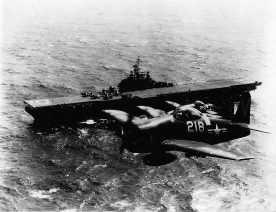 Two U.S. Navy F8F-2 Bearcats flyover the USS Valley Forge (CV 45). The white stripes on the fuselage of the aircraft are war game markings. National Museum of Naval Aviation photo