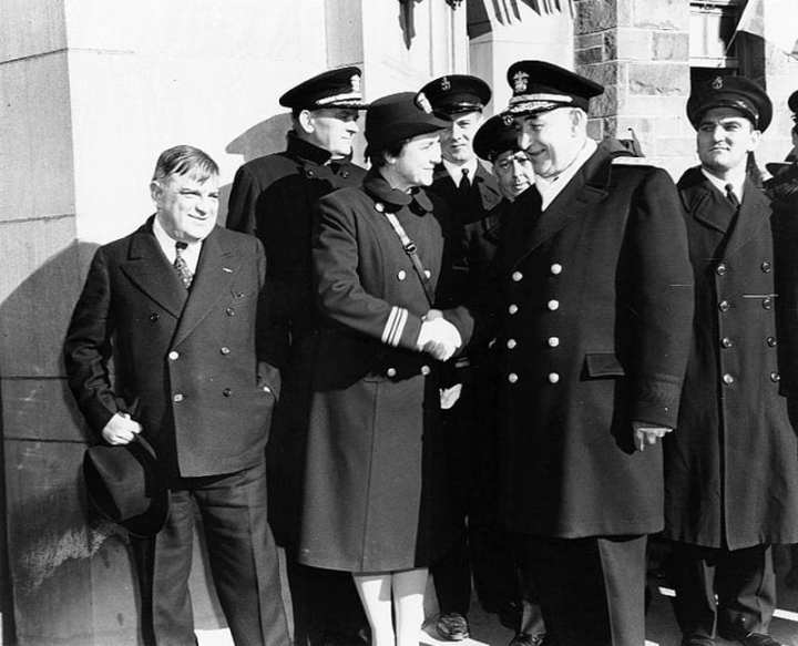 Commissioning ceremonies at the new training school for female Navy (WAVES) and Coast Guard (SPARS) Officers, circa early 1943. Standing in front are (left to right): Fiorello La Guardia, Mayor of New York City; Lt. Cmdr.  Mildred McAfee, USNR, Director of the WAVES; and Rear Adm. Randall Jacobs, USN, Chief of Naval Personnel. U.S. Naval Historical Center photo