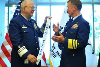 Coast Guard Commandant Adm. Paul Zukunft (right) presents a commemorative pennant to Commodore Thomas C. Mallison, the current national commodore of the U.S. Coast Guard Auxiliary. U.S. Coast Guard photo by Petty Officer 2nd Class Patrick Kelley