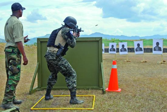 A member of a Honduran special operations team fires during a hostage scenario as part of the stress event during the Fuerzas Comando competition at Fort Tolemaida, Colombia, July 27, 2014. U.S. Army photo by Sgt. Wilma Orozco Fanfan
