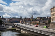 A modern highway sits against Stockholm's wide collection of centuries-old buildings and above one of its waterways. July 2015.