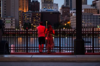 A couple stands beneath the neon lights of Station Square, looking across the Monongahela River to Pittsburgh. July 2015.