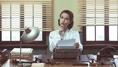 35506388 - pensive vintage woman with hand on chin, typing on typewriter and looking for inspiration