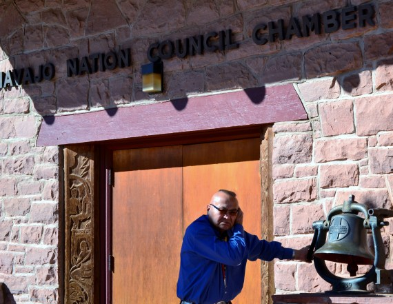 Navajo Nation Legislative Assistant Harold Morgan rings the bell in front of the Navajo Council chamber to call delegates to the chamber on Feb. 21, 2014. Photo by Marley Shebala