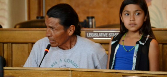Rocky Ridge community member Marshall Johnson pleads with Navajo Council Resources and Development Committee to approve agreement for study to pave remote bus route. His daughter, Mikayla Johnson, 10, tells committee about how her brother fell off bus seat when bus hit rocky portion of road.  RDC was meeting in Council chambers in Window Rock, Ariz., on July 8, 2014. Photo by Marley Shebala. (Please provide proper photo credit when reusing photo.)