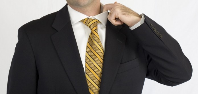 Businessman in black suit nervously adjusting collar