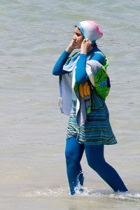 A woman dressed in a burkini walks in the water by the beach in Alexandria, Egypt. Giorgio Montersino/CC-flickr