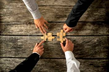 44155128-four-successful-business-men-joining-two-puzzle-pieces-each-being-held-by-two-partners-rustic-wooden