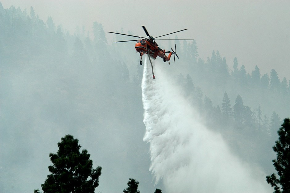 A helicopter drops water on a wildfire