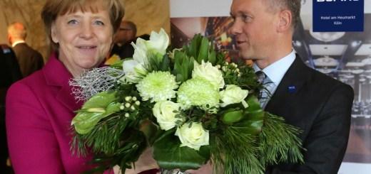 Ein Blumenstrauß für die Kanzlerin: Hoteldirektor Achim Laurs begrüßt Angela Merkel im Dorint Hotel am Heumarkt Köln.  Foto: Alois Müller – Dorint Hotels & Resorts/Abdruck honorarfrei