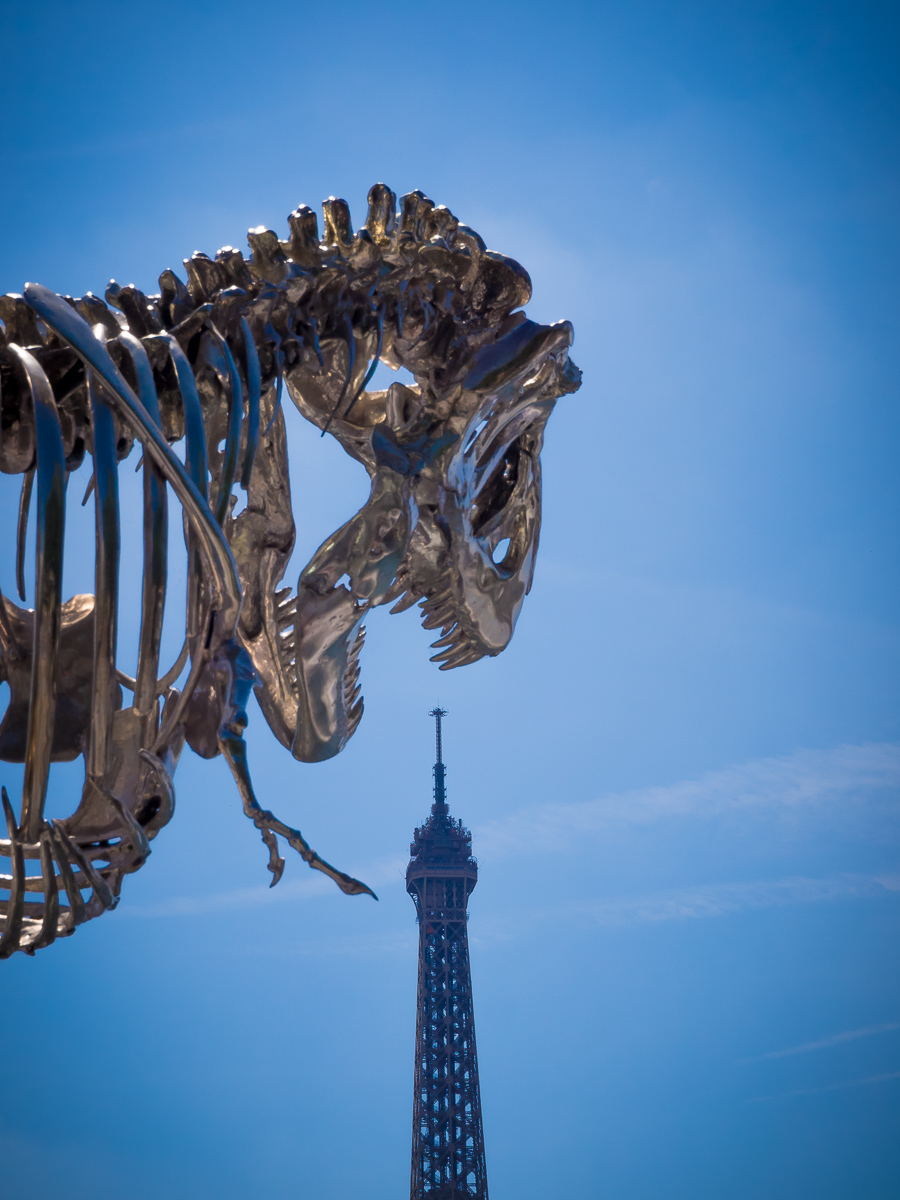 The top of the Eiffel Tower about to be bitten off  by a T'Rex sculpture.