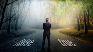 """(fotogestoeber/Shutterstock.com) 10SECRET-040616-shutterstock businessman has to decide which direction is better with the words """"false"""" and """"true"""" on the road"""