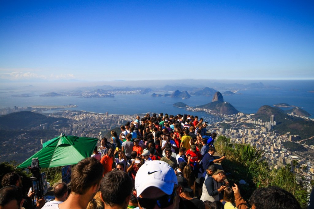 Hundreds of travelers admiring the view from the top of Corcovado Mountain.