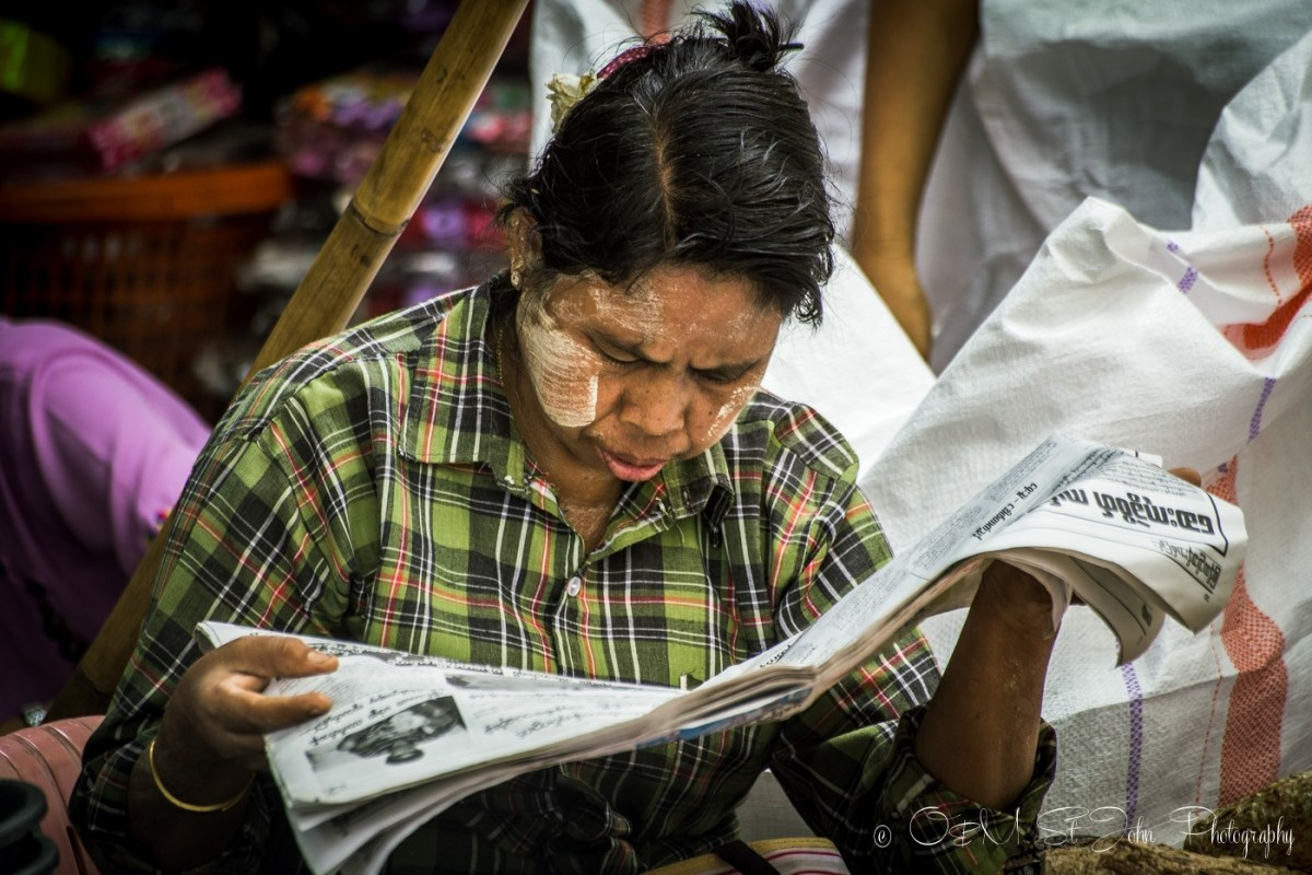 Woman with thanaka paste on her cheeks is reading a local newspaper. Yangon, Myanmar