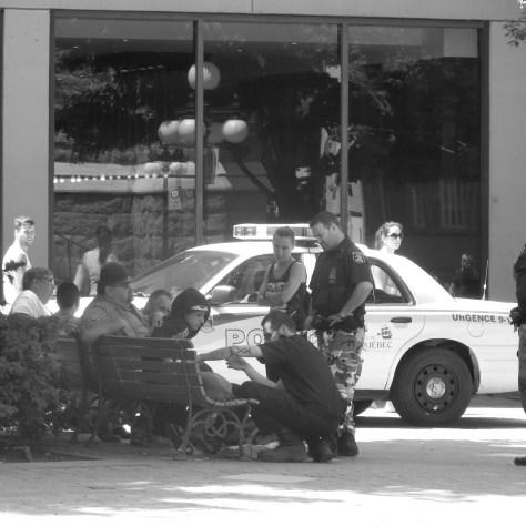 Sur cette photo du Parvis St-Roch, deux policiers de la Ville et un travailleur de la SPCA vérifient la condition physique du chien d'une jeune itinérante. L'opération a duré près de deux heures. L'auto-patrouille bloque entièrement le chemin piétonnier reliant la rue St-François à la rue St-Joseph Photo: Gilles Simard