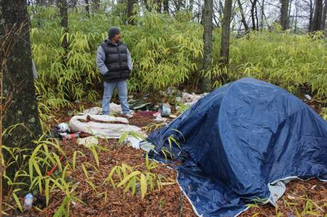 John looks at his tent, its contents strewn on the ground. Someone recently stole his heater out of the tent and threw the couple's belongings outside. (Staff photo by Caitlin Owens)