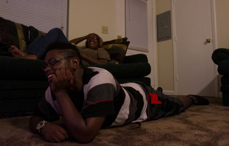 Darrius and Shameka laugh while enjoying watching a movie together as a family on their first night in the townhome. Rhamir cooked dinner so his mom would finally just be able to lie down and relax.
