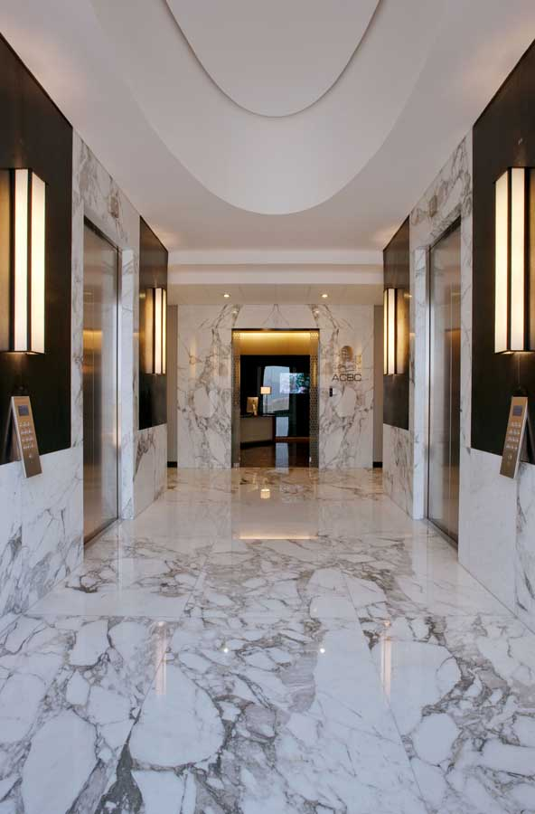 Combine modern lighting, dark paneling and our Arabescato Marble