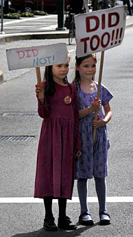 girls holding signs blaming each other