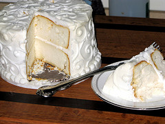 white wedding cake with slice removed