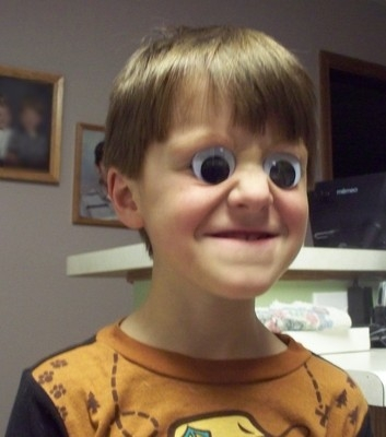 boy with googly eyes grinning